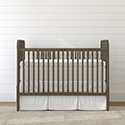 empty brown crib against a white background