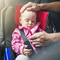 Baby being secured in car seat